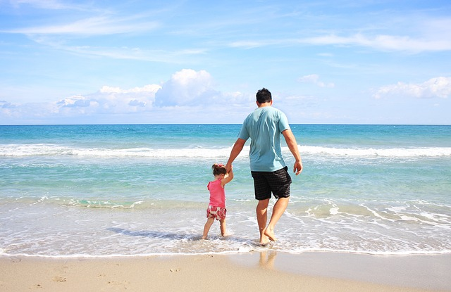man and child walking along the beach